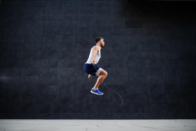 Vista laterale dell'uomo caucasico muscolare bello in breve e salto della maglietta davanti alla parete grigia all'aperto.