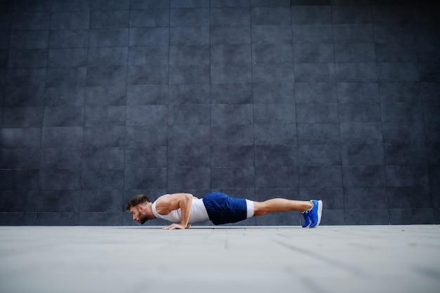Vista laterale dell'uomo caucasico muscoloso bello in pantaloncini corti e maglietta facendo flessioni. sullo sfondo è il muro grigio.