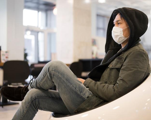 Vista laterale dell'uomo che bighellona mentre indossa una maschera medica