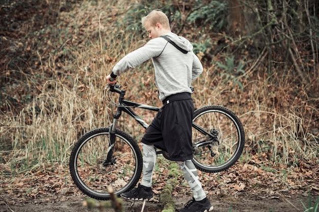 Vista laterale dell'uomo che cammina con la sua bicicletta