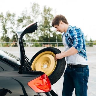 Vista laterale dell'uomo che elimina la ruota di scorta