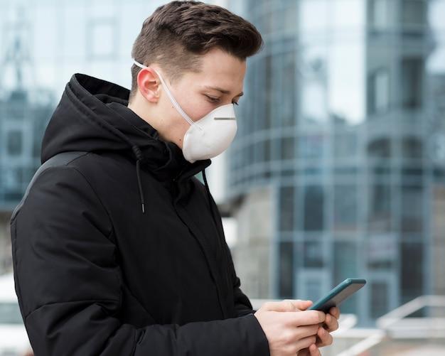 Vista laterale dell'uomo che esamina il suo telefono mentre indossa una maschera medica