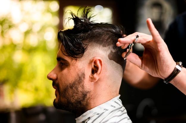 Vista laterale dell'uomo che fa tagliare i capelli