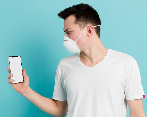 Vista laterale dell'uomo che indossa maschera medica e che ostacola il suo smartphone