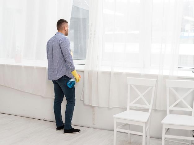 Vista laterale dell'uomo che osserva attraverso la finestra mentre pulendo