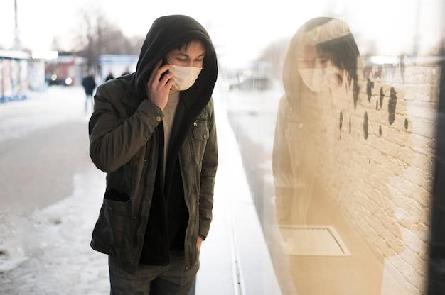 Vista laterale dell'uomo che parla al telefono mentre indossa maschera medica