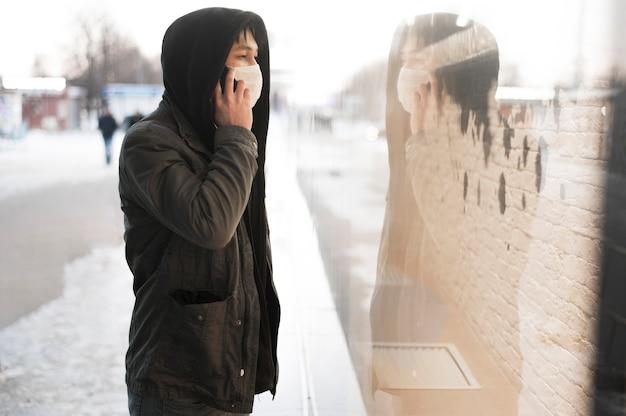 Vista laterale dell'uomo che parla al telefono mentre indossa una maschera medica fuori
