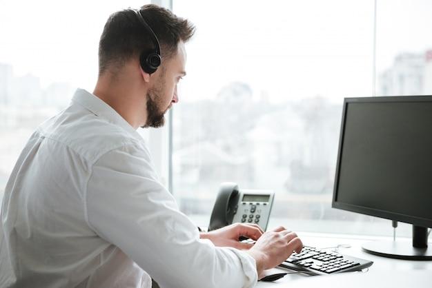 Vista laterale dell'uomo che per mezzo del computer