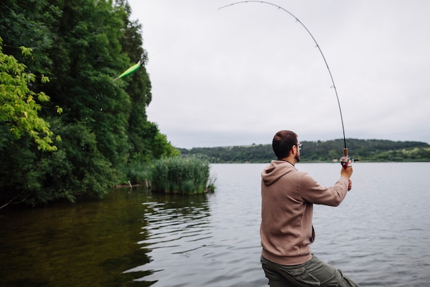 Vista laterale dell'uomo che pesca nel lago