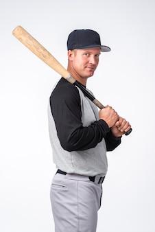 Vista laterale dell'uomo che posa con la mazza da baseball