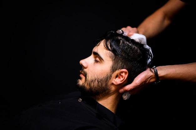 Vista laterale dell'uomo che si lava i capelli
