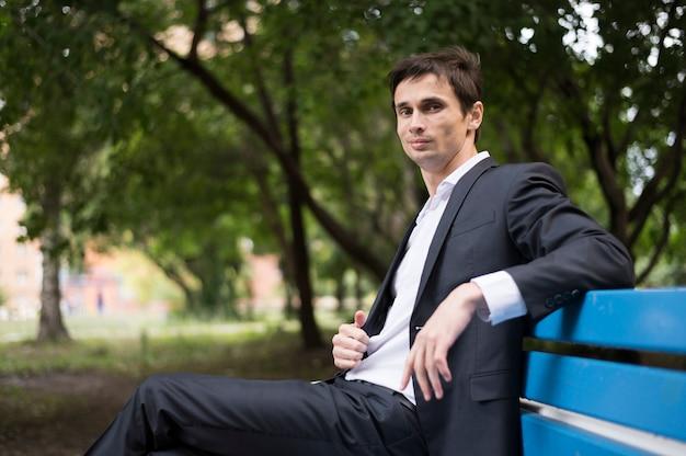 Vista laterale dell'uomo che si siede sul banco blu