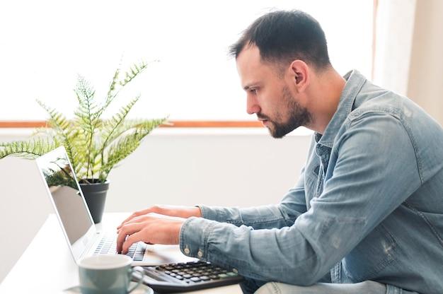 Vista laterale dell'uomo che wotking al suo computer portatile