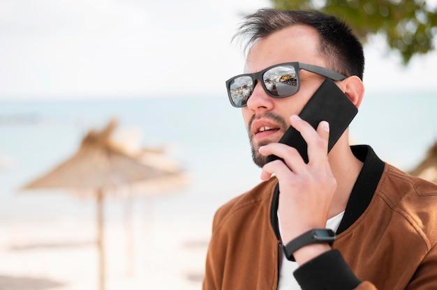 Vista laterale dell'uomo con gli occhiali da sole che parla sullo smartphone