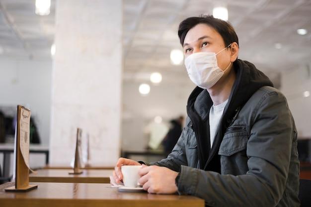 Vista laterale dell'uomo con la mascherina medica che si siede ad una tabella per avere caffè