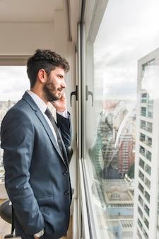 Vista laterale dell'uomo d'affari che sta vicino alla finestra dell'ufficio che parla sul telefono cellulare