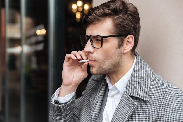 Vista laterale dell'uomo d'affari in occhiali e cappotto
