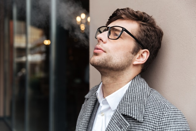 Vista laterale dell'uomo d'affari piacevole in occhiali e cappotto