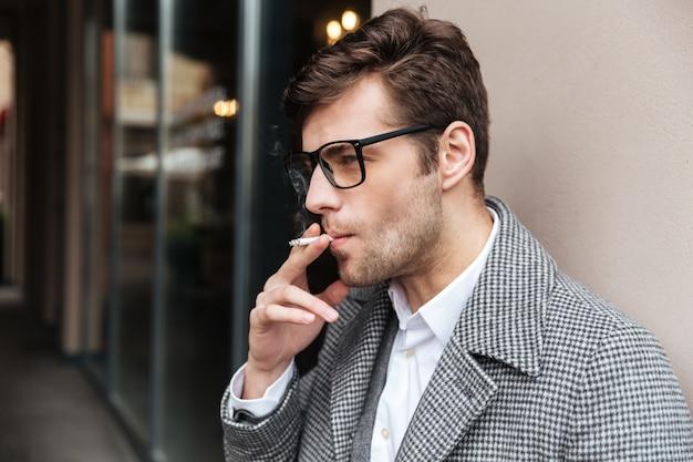 Vista laterale dell'uomo d'affari serio in occhiali e cappotto