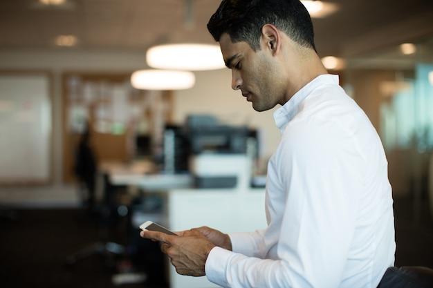 Vista laterale dell'uomo d'affari utilizzando il telefono cellulare