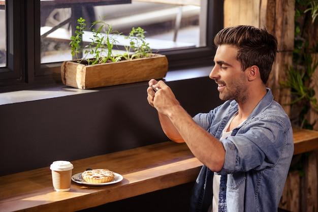 Vista laterale dell'uomo dei pantaloni a vita bassa che prende foto del suo pasto