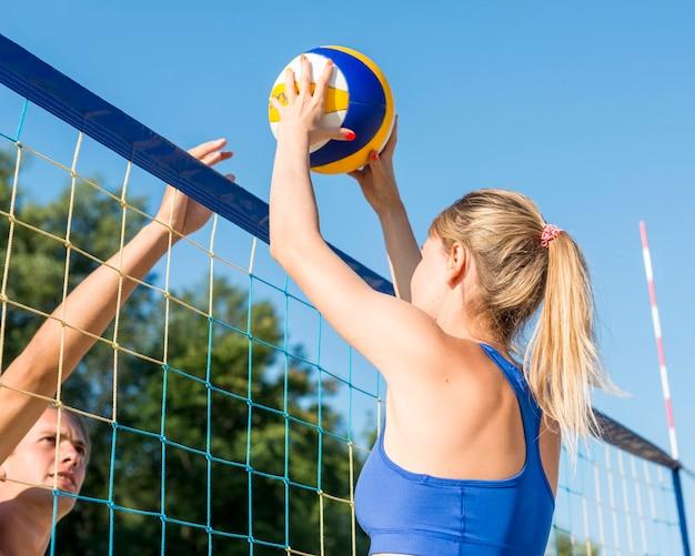 Vista laterale dell'uomo e della donna che giocano a beach volley