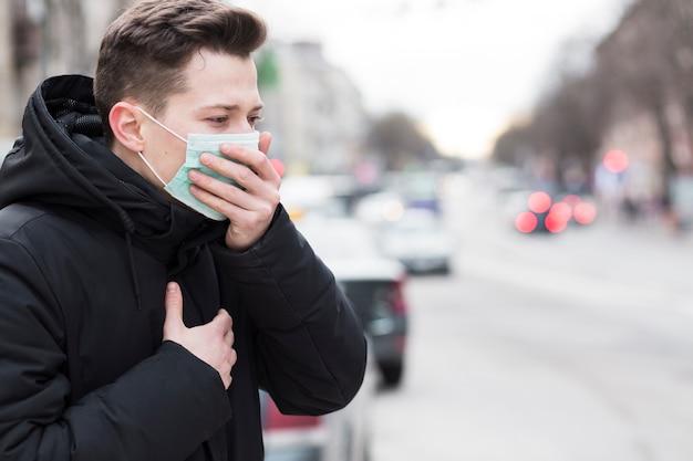 Vista laterale dell'uomo in città che tossisce mentre indossa una maschera medica