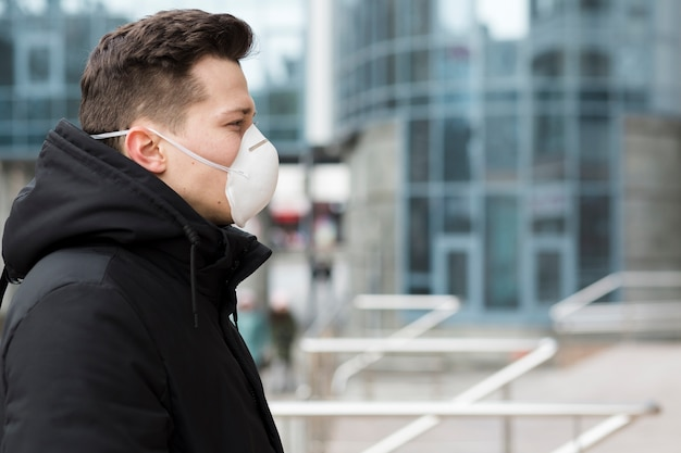 Vista laterale dell'uomo in città con maschera medica e copia spazio