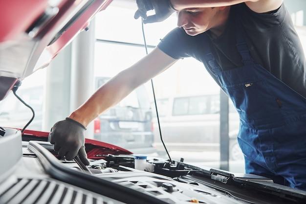 Vista laterale dell'uomo in uniforme che funziona con l'automobile rotta. concezione del servizio auto