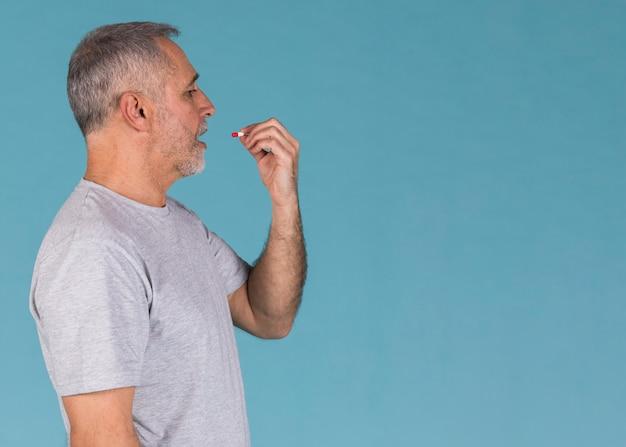 Vista laterale dell'uomo malato che prende capsula contro fondo blu