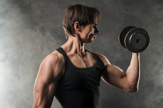 Vista laterale dell'uomo muscoloso che tiene peso