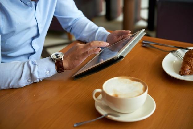 Vista laterale dell'uomo potato che utilizza applicazione mobile sul pc della compressa che mangia caffè con il croissant