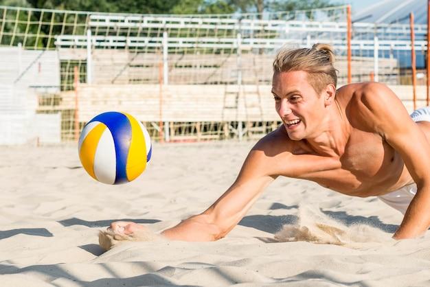 Vista laterale dell'uomo senza camicia che raggiunge per colpire la pallavolo prima che colpisca la sabbia
