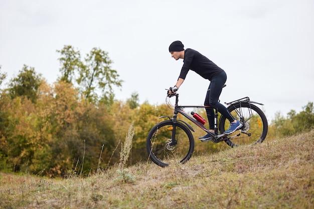 Vista laterale dell'uomo sportivo in sella a mountain bike su pista enduro, ragazzo abiti tuta nera e berretto, cavalcando hiil nella foresta