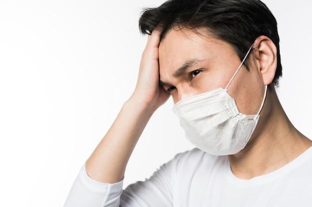 Vista laterale dell'uomo triste che tocca la sua testa mentre indossando maschera medica