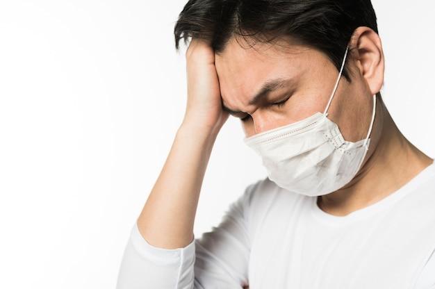 Vista laterale dell'uomo triste con coronavirus che indossa una maschera medica