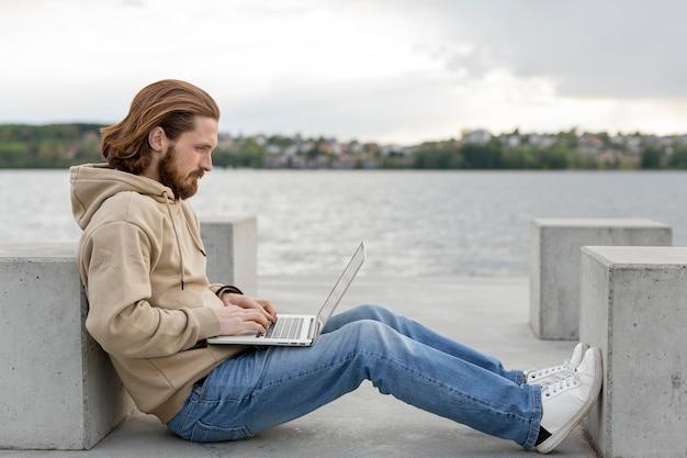 Vista laterale dell'uomo vicino al lago che lavora al computer portatile