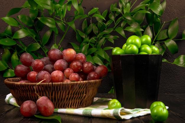 Vista laterale dell'uva dolce fresca in un canestro di vimini e una ciotola con le prugne verdi acide su superficie di legno sulla tavola delle foglie verdi