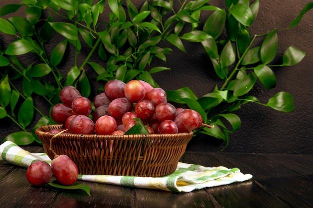 Vista laterale dell'uva dolce fresca in un canestro di vimini su superficie di legno sulla tavola delle foglie verdi