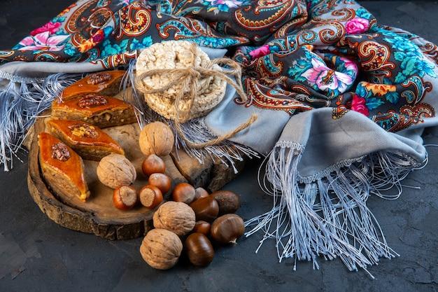 Vista laterale della baklava con noci intere e pani di riso sullo scialle con fiocco