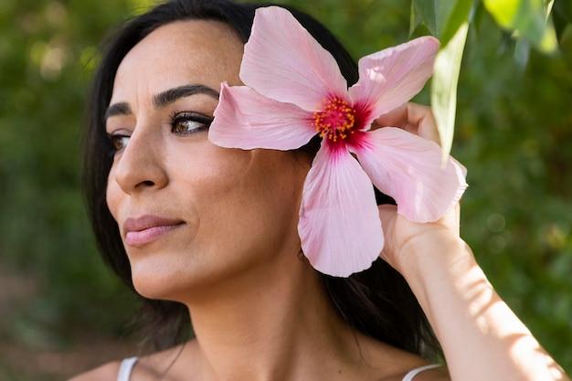Vista laterale della bella donna all'aperto con fiori nei capelli