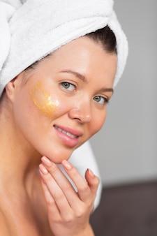 Vista laterale della bella donna che applica la cura della pelle con un asciugamano sulla testa