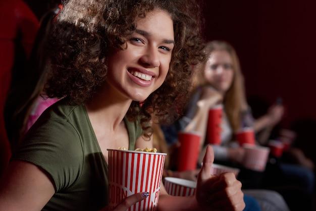 Vista laterale della bella donna sorridente con i capelli ricci volumed guardando, sala cinema, con gustosi popcorn. giovane ragazza emozionalmente castana che guarda film divertente al cinema moderno.