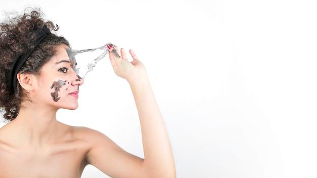 Vista laterale della bella giovane donna rimozione maschera facciale nera