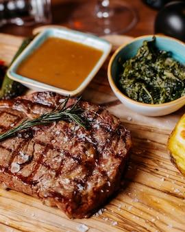 Vista laterale della bistecca di manzo alla griglia con salsa su una tavola di legno