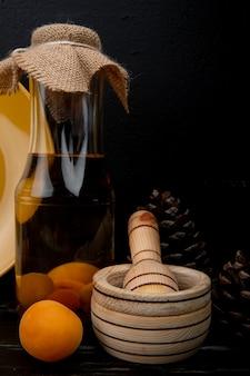 Vista laterale della bottiglia di composta di albicocche e frantoio di aglio con albicocca e pigne su superficie di legno e fondo nero