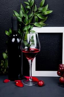 Vista laterale della bottiglia e bicchiere di vino rosso con cornice e foglie con petali di fiori su fondo nero con copia spazio