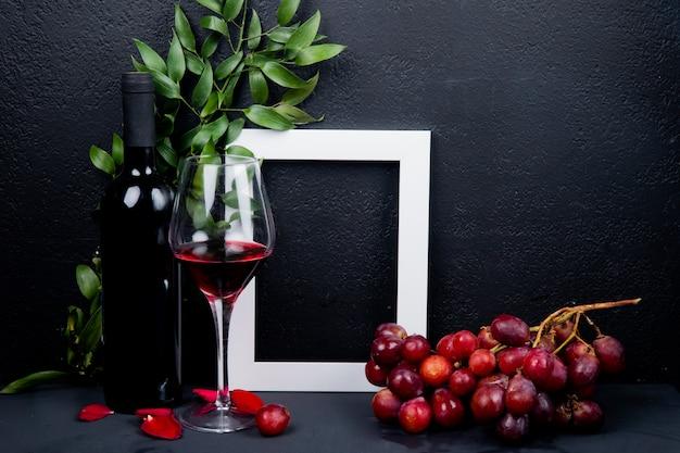 Vista laterale della bottiglia e bicchiere di vino rosso con telaio di uva e foglie con petali di fiori su fondo nero con copia spazio
