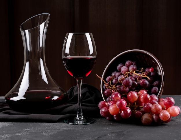 Vista laterale della brocca con vino rosso e l'uva sull'orizzontale scuro