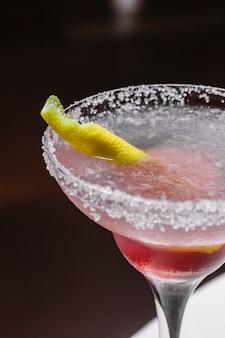 Vista laterale della buccia di limone del sale della fragola della calce del liquore rosso di tequila della margarita